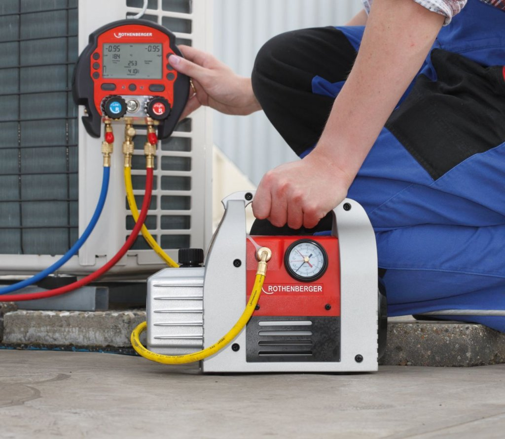 Koeltechnieker die airco buiten unit vacummeert en koelmiddel vult op de installatie